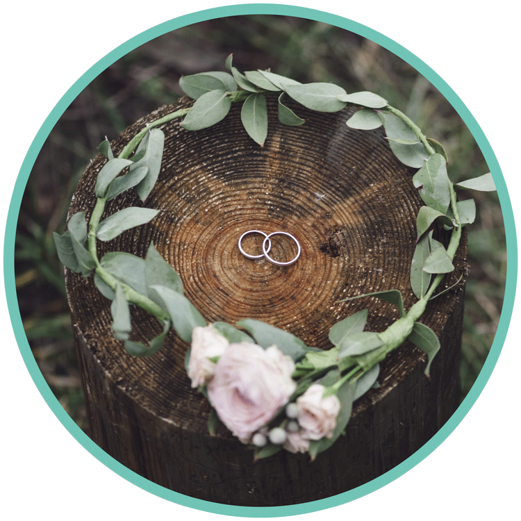 Wedding rings with flowers in a wooden slice